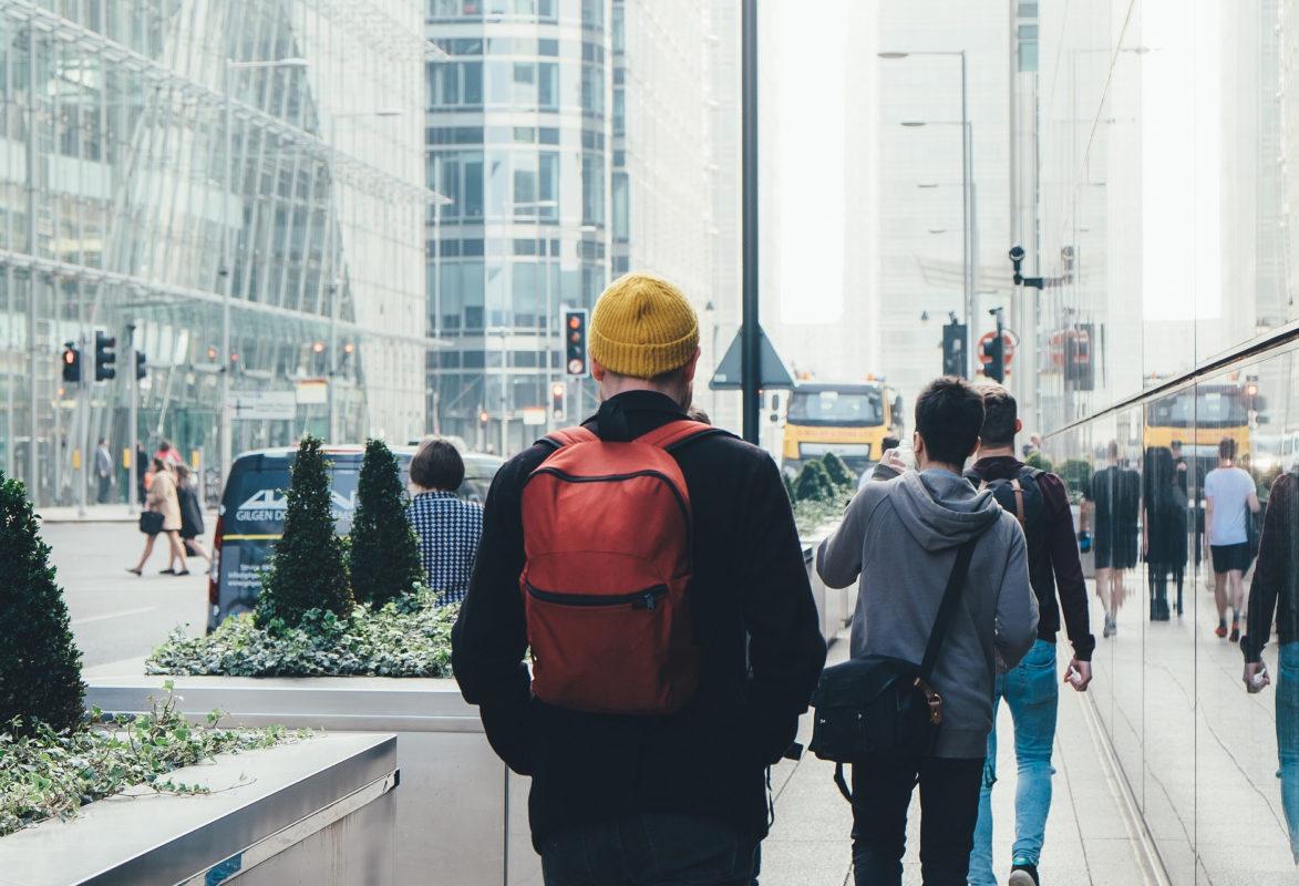 man with backback walking on urban sidewalk