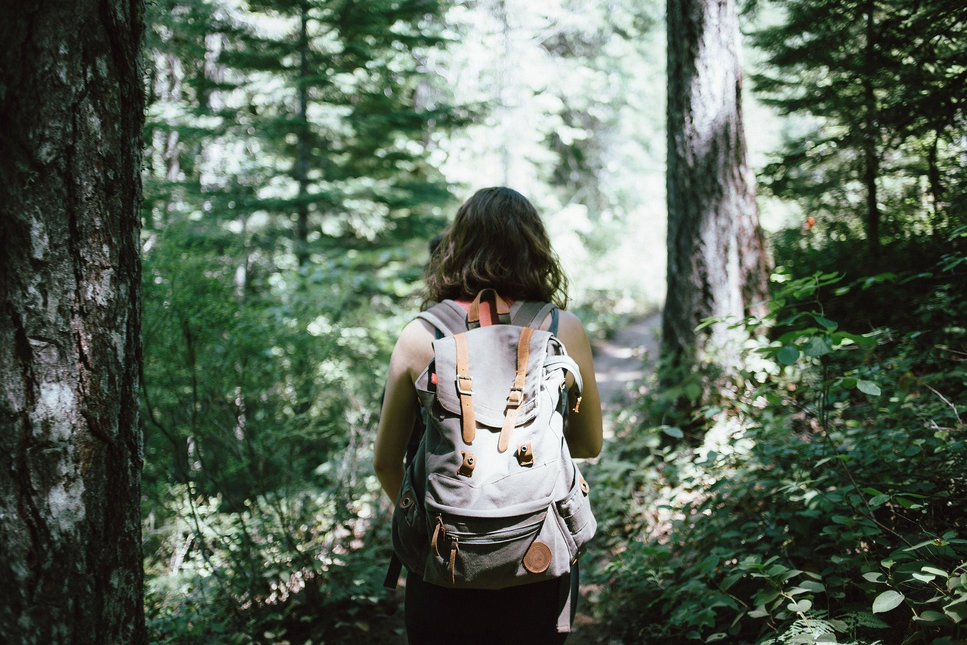 woman with backback walking in a forest