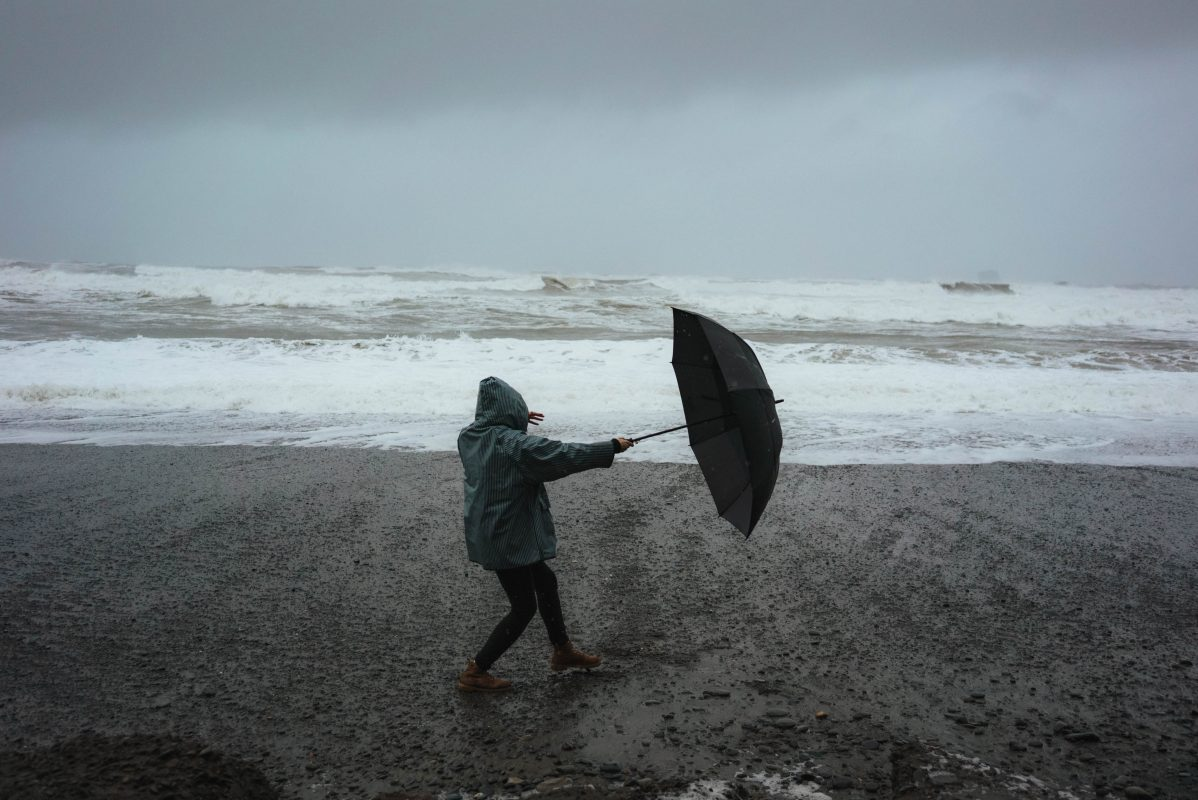 unknown person seaside with umbrella fighting against the wind